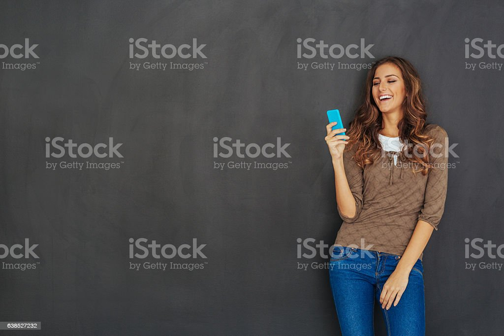Beautiful woman texting in front of an empty blackboard stock photo
