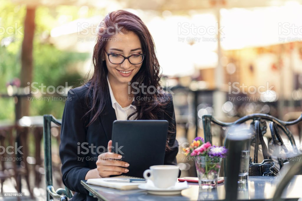 Beautiful woman texting on her digital tablet stock photo
