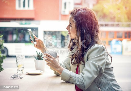 Lovely young woman having coffee break and chatting on her phone