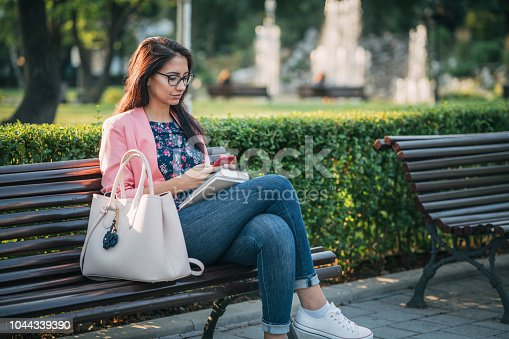 Young attractive woman relaxing in the park and browsing on her mobile phone
