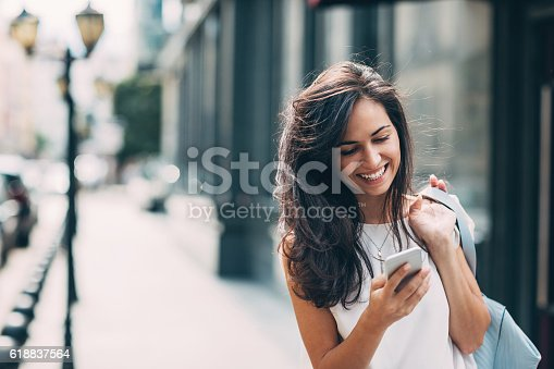 istock Beautiful woman texting on the street 618837564