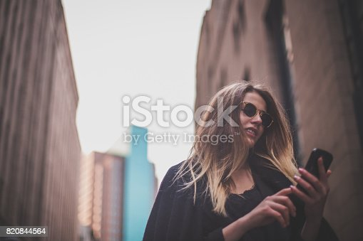 istock Beautiful woman texting outdoors 820844564