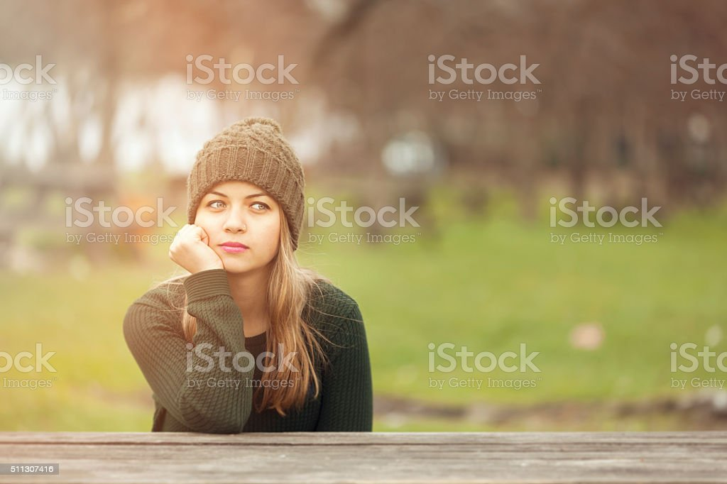 Beautiful woman thinking outside in park stock photo