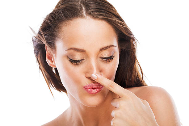 Schöne Frau berühren Ihre Nase.   Isoliert auf weiß. – Foto