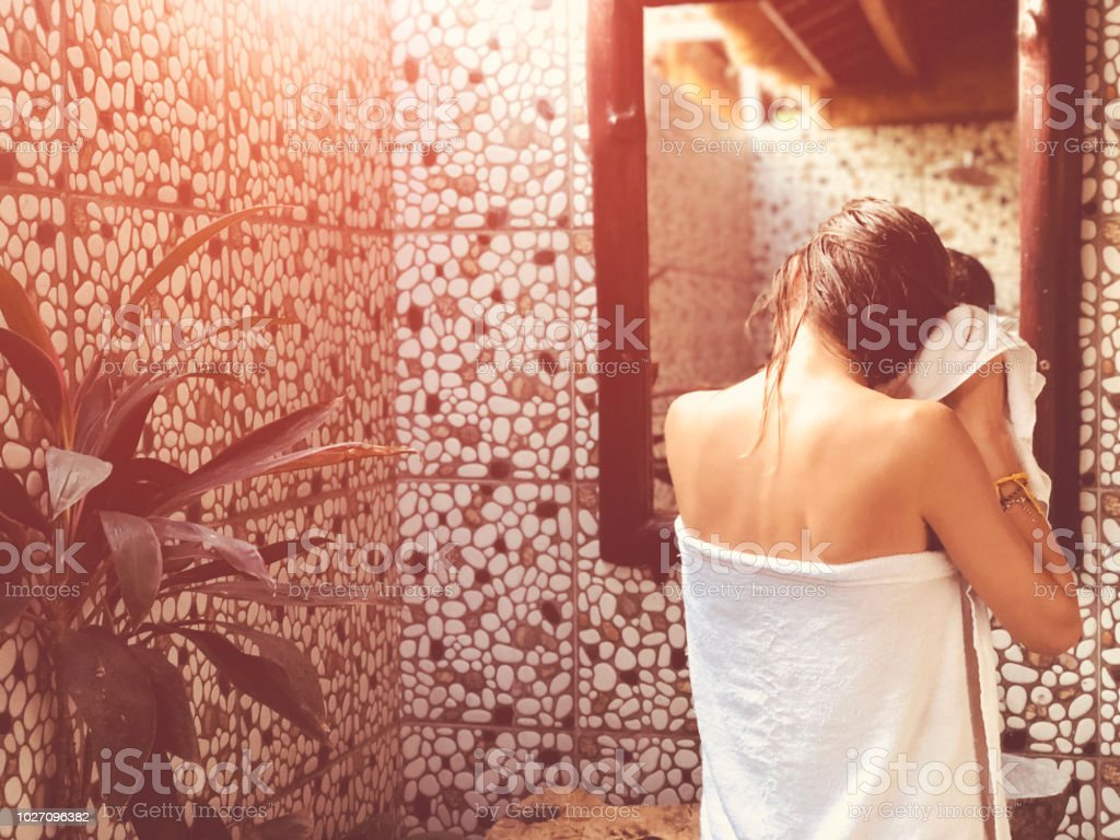 Beautiful woman touching wet hair while looking in the mirror in bathroom. stock photo