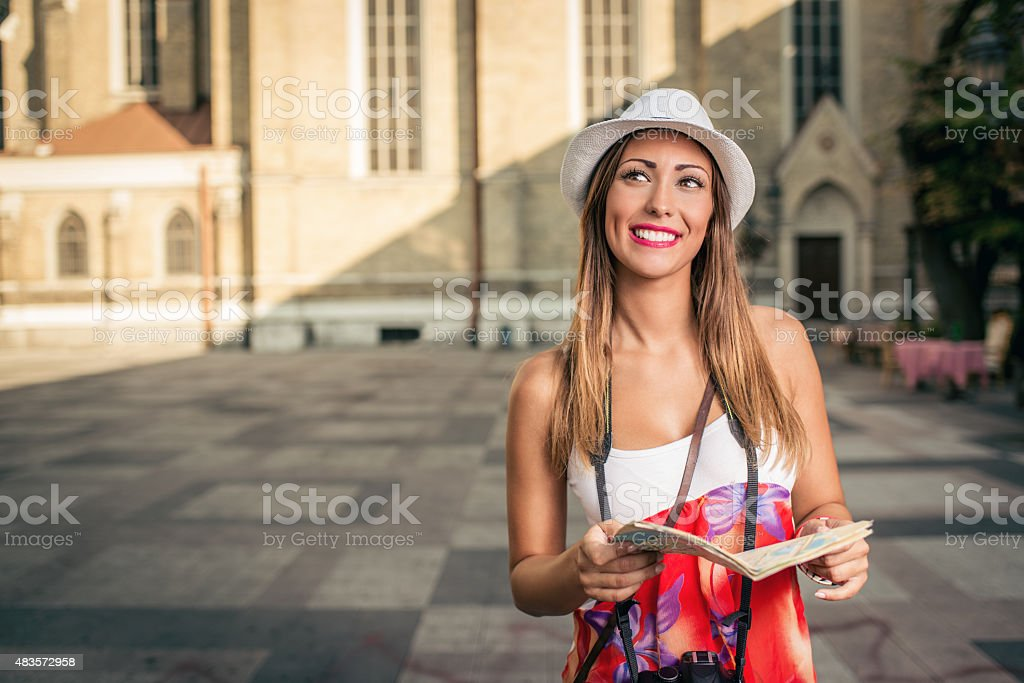 Beautiful Woman Tourist Happy woman on vacation walking and studying map of city. 2015 Stock Photo