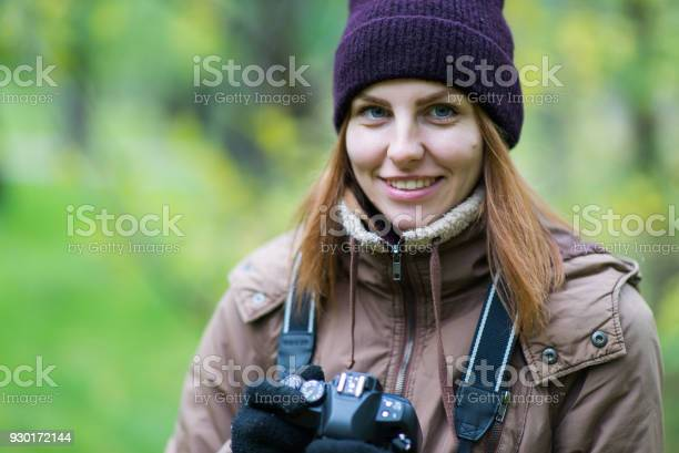Photo of beautiful woman tourist travel photographer photographing forest at autumn day
