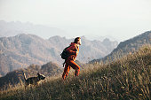 istock Beautiful woman traveler climbs uphill with a dog on a background of mountain views. 1209875463