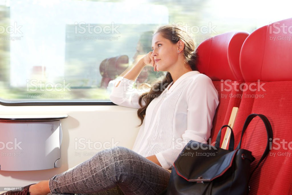 beautiful woman traveling by train looking out the window stock photo