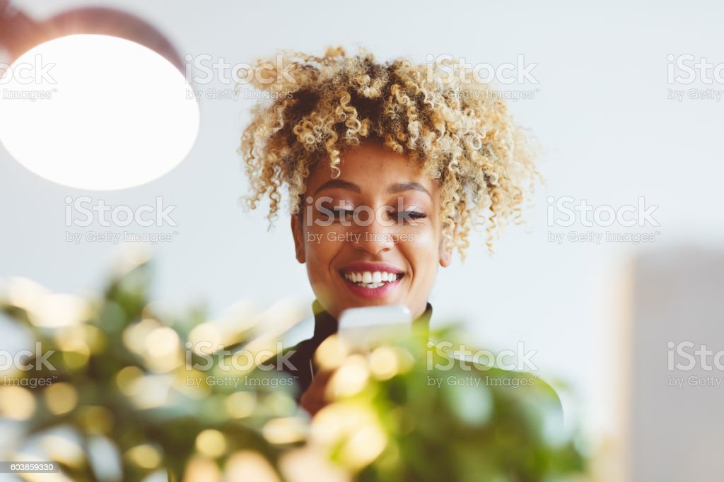 Beautiful woman typing on mobile indoors Afro american beautiful young woman typing on smart phone indoors, smiling, focus on face. Adult Stock Photo