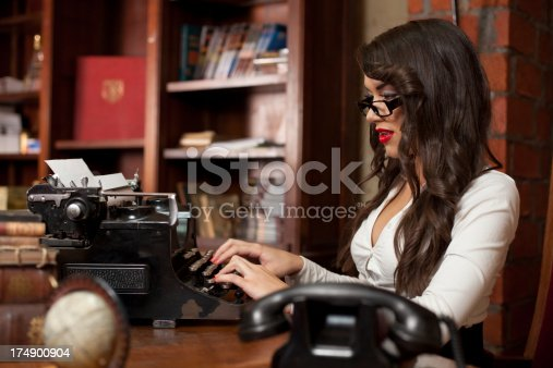 471445335istockphoto Beautiful woman typing on the old typewriter 174900904