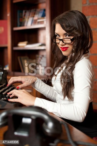 471445335istockphoto Beautiful woman typing on the old typewriter 471445335