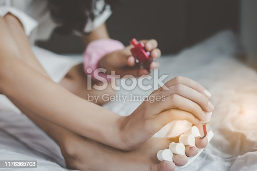 istock Beautiful woman use red color nail polish for painting her beautiful toenail, pedicure in morning at home, smiley face. Charming beautiful woman love to painted her nails, pedicure, She feel happy 1176365703