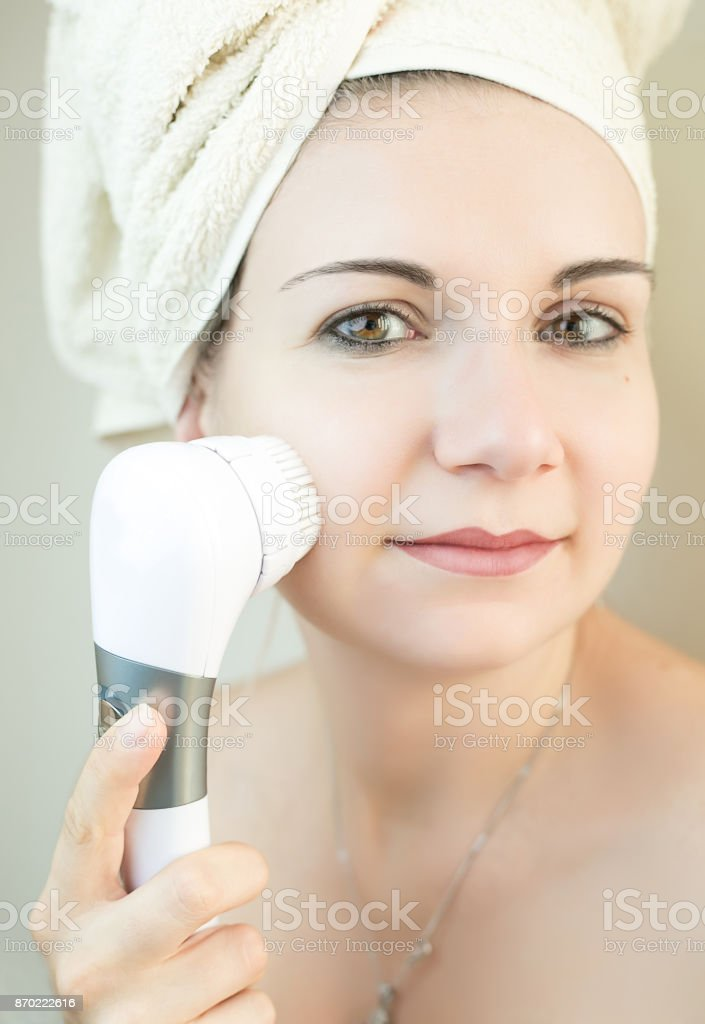 Beautiful woman using a facial cleaning brush machine to clean deep her skin. Woman health tools concept. stock photo