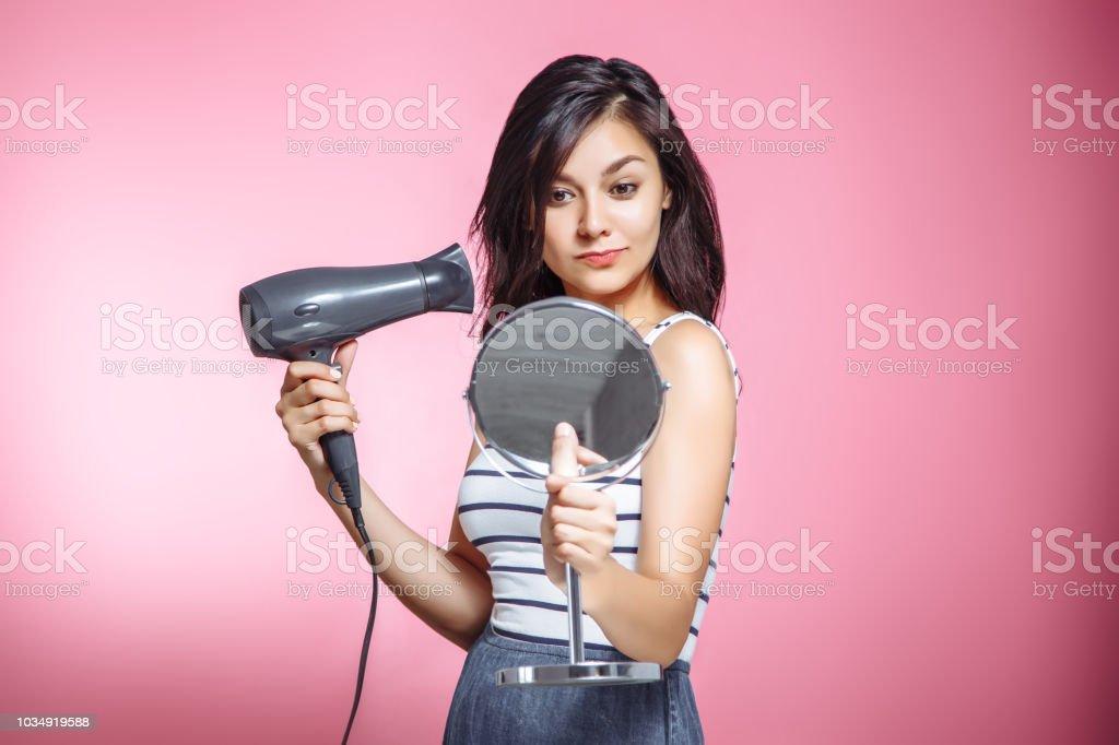 Mulher bonita usando um secador de cabelo e sorrindo enquanto olha para o espelho em um fundo rosa. - foto de acervo