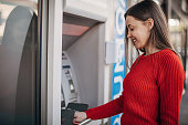 istock Beautiful woman using ATM machine on the street 1286070123