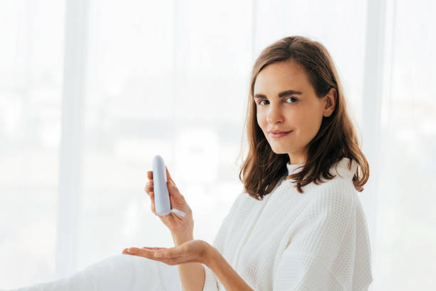 Beautiful woman using cream at home stock photo