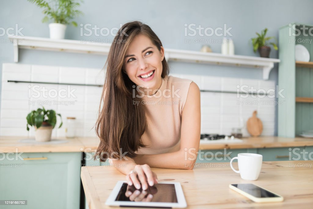 Beautiful woman using digital tablet at home Beautiful student girl working with digital tablet computer. Work, study, distance education, e-learning, studying freelance concept 20-29 Years Stock Photo