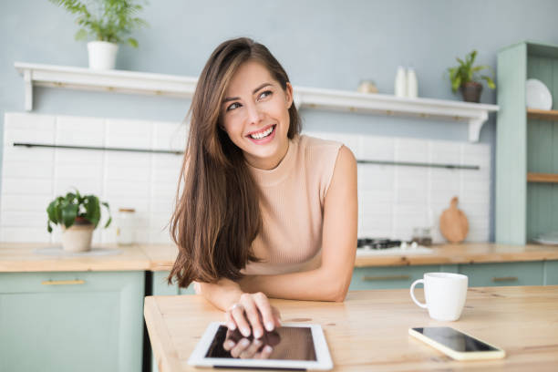 Beautiful woman using digital tablet at home stock photo