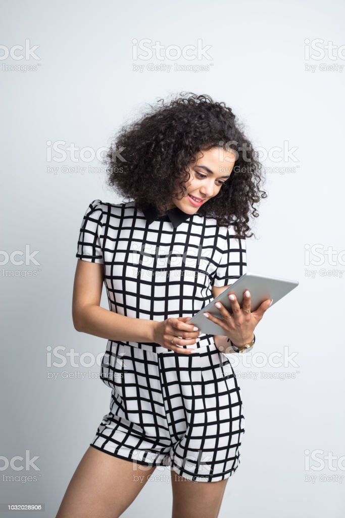 Beautiful woman using digital tablet Beautiful woman in casual outfit looking at digital tablet in hand against gray background 20-24 Years Stock Photo