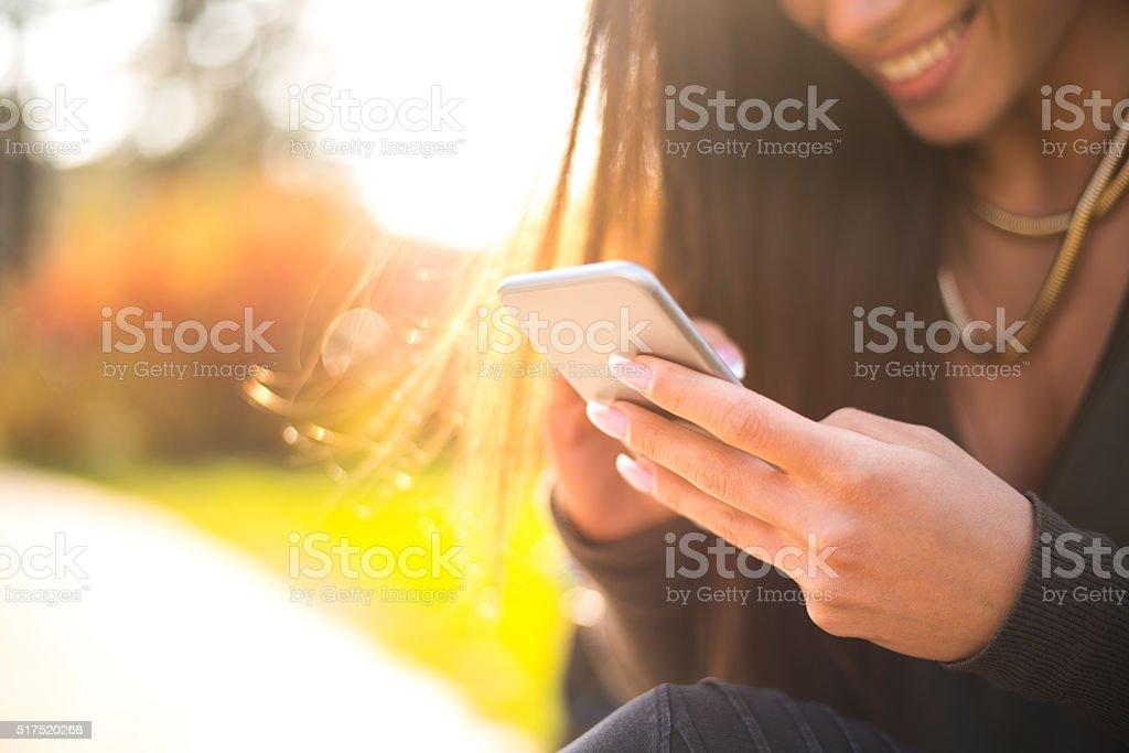 Beautiful woman using her smartphone outside stock photo