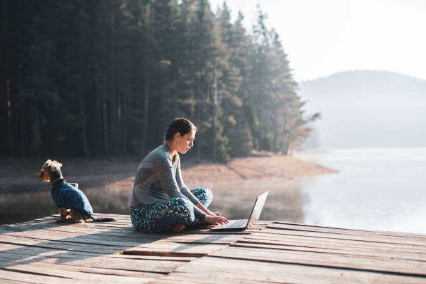 Beautiful woman using laptop in nature