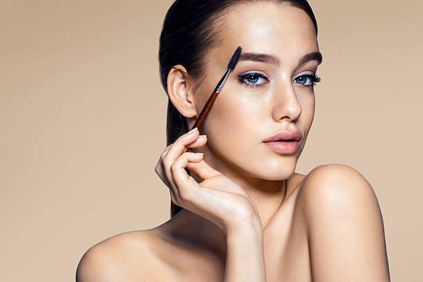 Beautiful woman using mascara stock photo