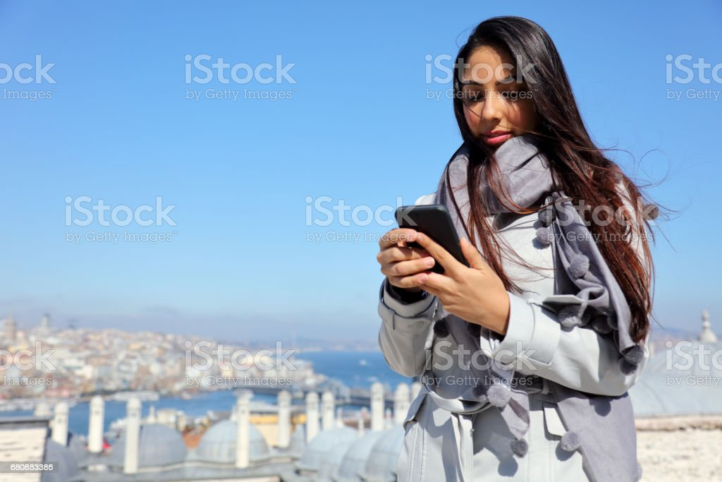 Beautiful woman using mobile phone at the Suleymaniye Mosque enjoying the amazing view of Istanbul, Turkey royalty-free stock photo