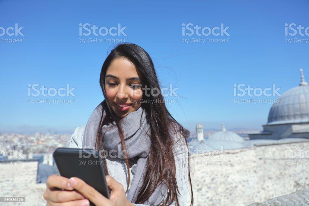 Beautiful woman using mobile phone at the Suleymaniye Mosque enjoying the amazing view of Istanbul, Turkey royalty-free stock photo