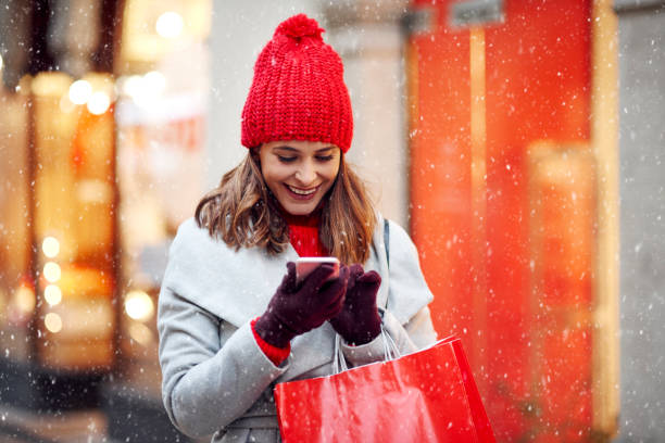 beautiful woman using mobile phone during shopping in wintertime - shopping стоковые фото и изображения