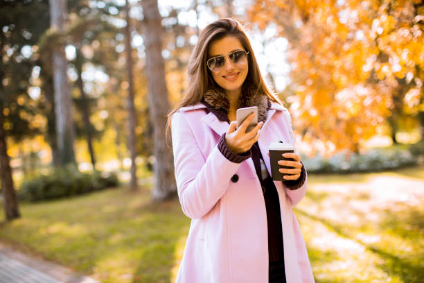 Beautiful woman using phone and drink coffee in autumn park stock photo