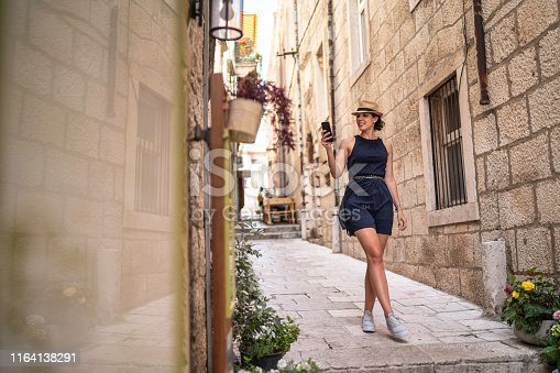 Beautiful woman using phone and walking in Dubrovnik, Croatia