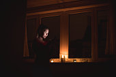 Beautiful woman using phone in dark room