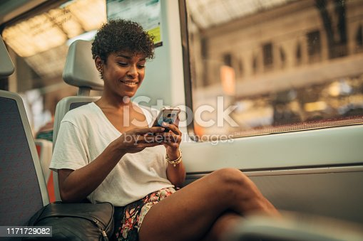 One woman, beautiful young lady riding in train, using mobile phone.