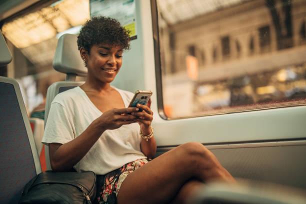 Beautiful woman using phone in train stock photo