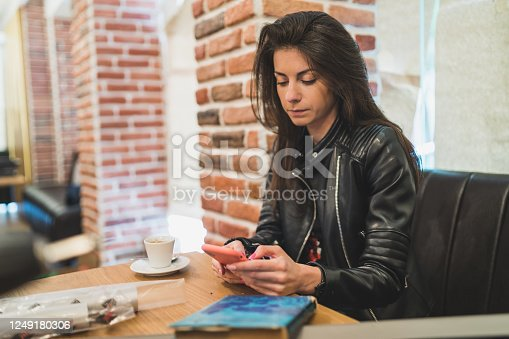 istock beautiful woman using smartphone for online shoping in coffee shop 1249180306