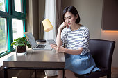 beautiful woman using smartphone with a laptop on desk at home.