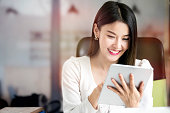 istock Beautiful woman using tablet while sitting at office desk. 1142615301