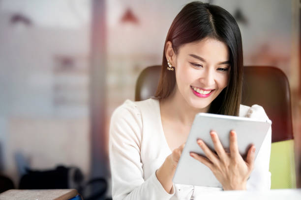 beautiful woman using tablet while sitting at office desk. - ásia imagens e fotografias de stock