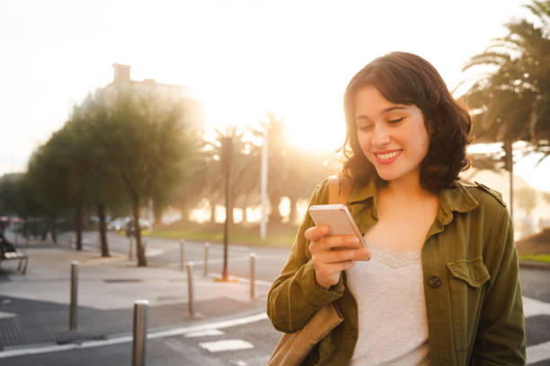 Beautiful woman using the smart phone in the city stock photo