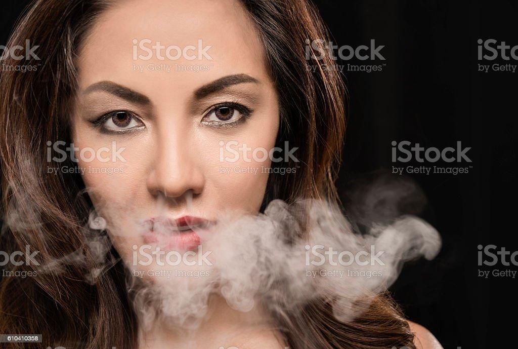 Beautiful woman vaping with smoke. stock photo