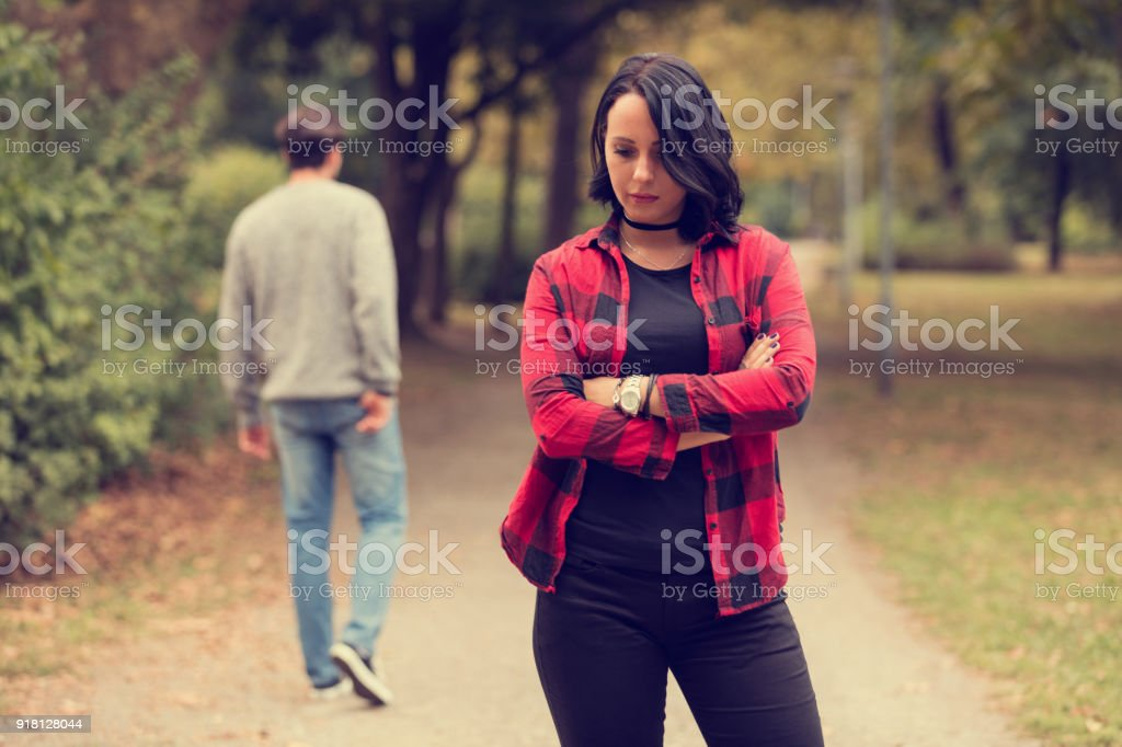 Beautiful woman waiting for boyfriend outdoors. Love or break up concept. stock photo