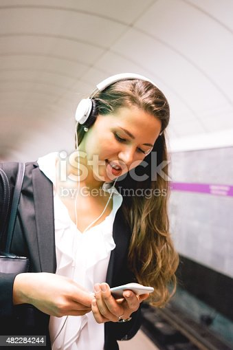 Beautiful woman listening to music from her smartphone while waiting for subway train.