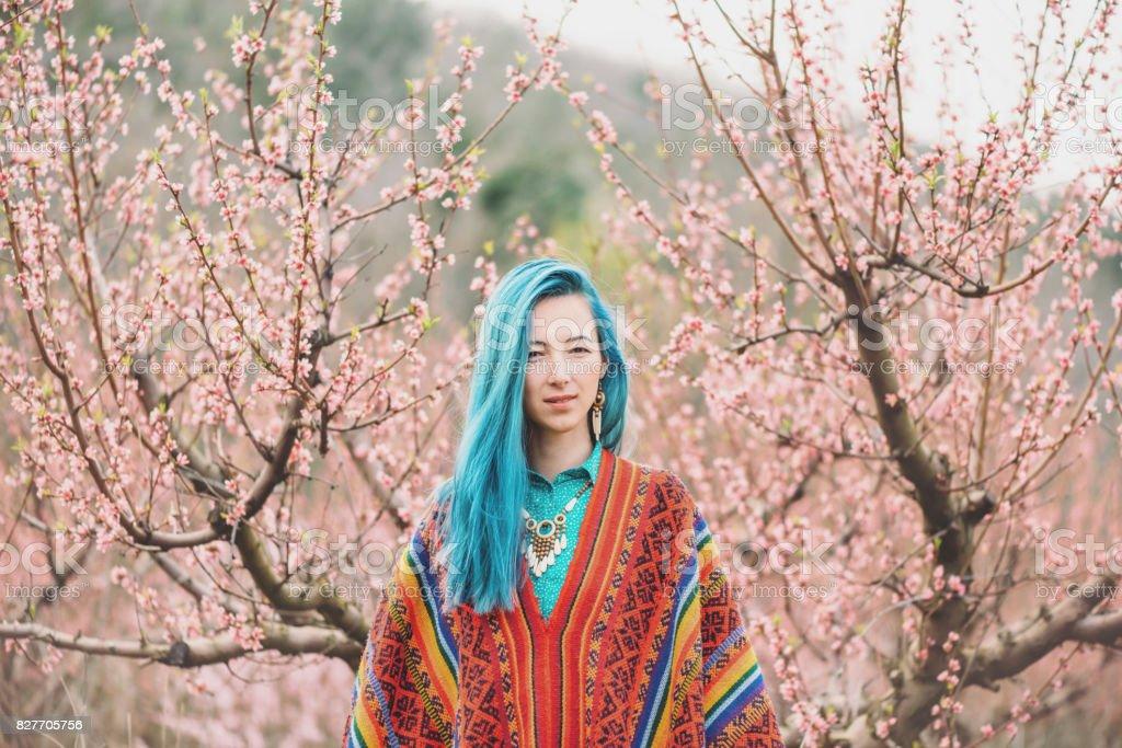 Belle femme marchant parmi les arbres en fleurs. - Photo