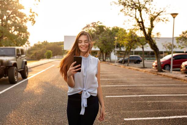 Beautiful woman walking and using smartphone stock photo