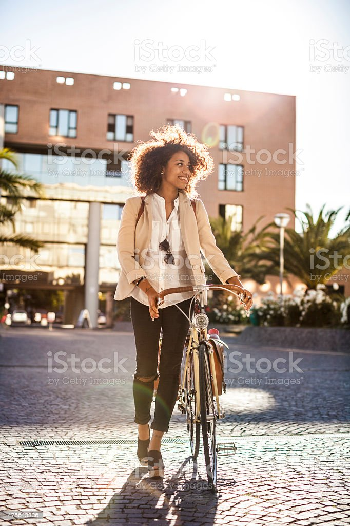 Beautiful woman walking holding her bicycle in the city stock photo