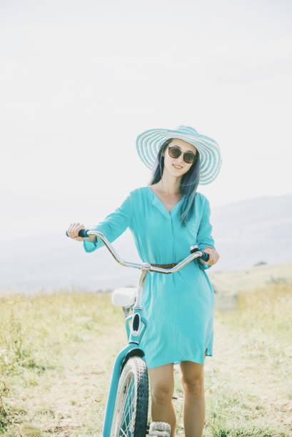 Belle femme marchant avec vélo en plein air. - Photo