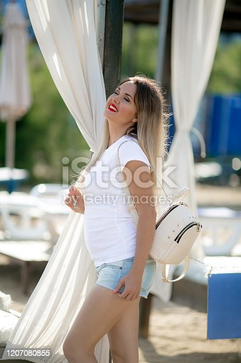 1054970060 istock photo A beautiful woman walks in summer short denim shorts with a white backpack on her back 1207080855