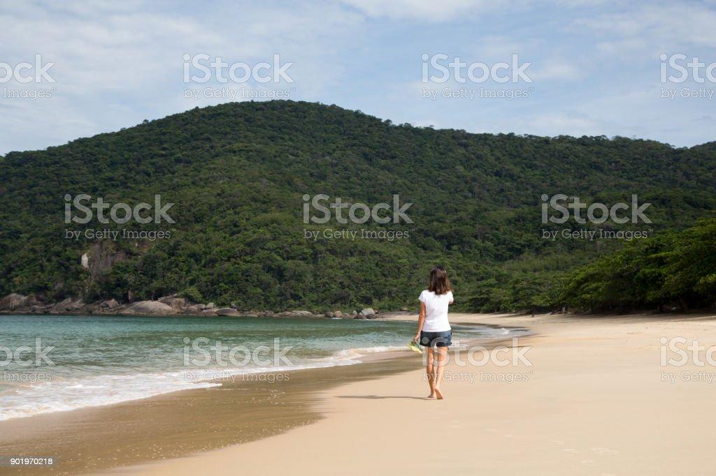 Beautiful woman walks on deserted beach in Brazil. stock photo