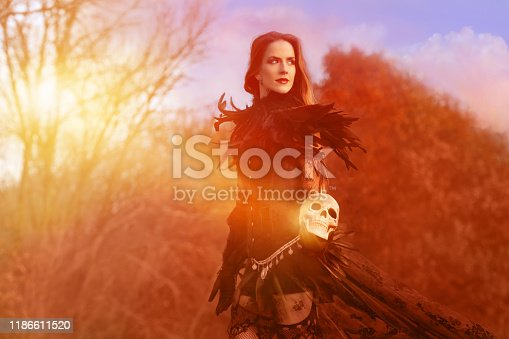 Beautiful woman warrior with human skull in autumn forest